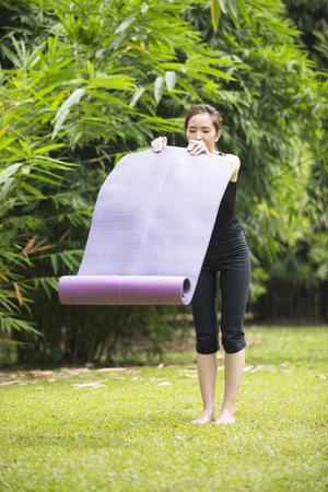 femme asiatique portant sur son tapis de yoga, se prépare à la pratique du yoga en plein air. mode de vie sain et de détente