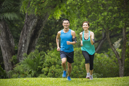 asian lifestyle: Athletic Asian man and woman running outdoors. Action and healthy lifestyle concept.