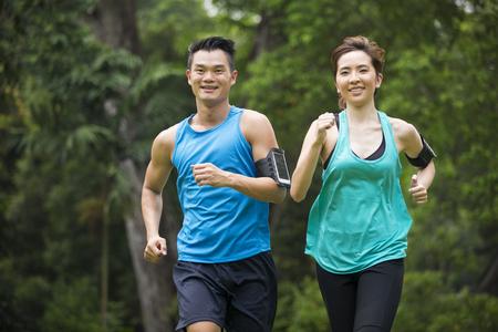hacer footing: Hombre asiático atlético y una mujer corriendo al aire libre. Acción y el concepto de estilo de vida saludable. Foto de archivo
