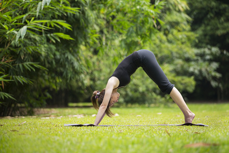 asian lifestyle: Asian woman wearing black clothes, practicing yoga in a garden. healthy lifestyle and relaxation