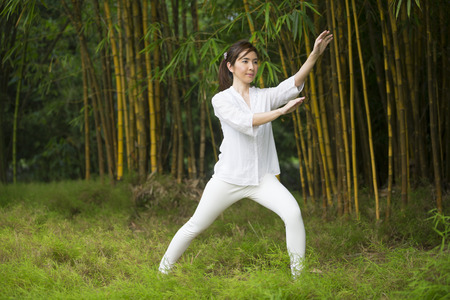 Asian woman practicing Tai Chi in a garden. healthy lifestyle and relaxation Stock Photo