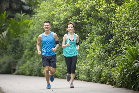 jog: Athletic Asian man and woman running outdoors. Action and healthy lifestyle concept.