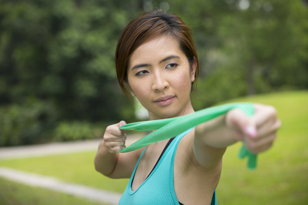 resistance: Athletic Asian woman exercising with a resistance band. Action and healthy lifestyle concept. Stock Photo
