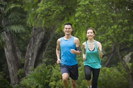 correr: Hombre asiático atlético y una mujer corriendo al aire libre. Acción y el concepto de estilo de vida saludable. Foto de archivo