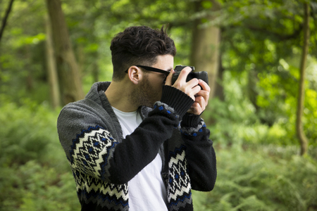 outside shooting: Portrait of man taking landscape photos with a DSLR in a forest. Caucasian Photographer shooting outside with digital camera.