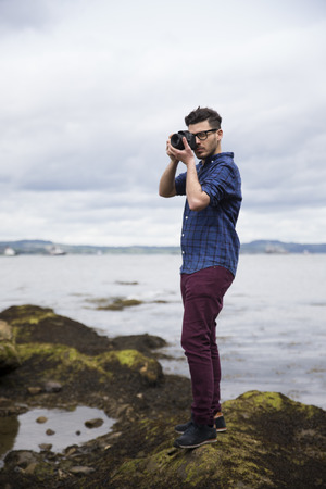 outside shooting: Portrait of man taking landscape photos with a DSLR at the coast. Caucasian Photographer shooting outside with digital camera.