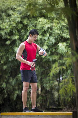 atleta corriendo: Asian man out running, using his smart watch heart rate monitor. Fitness healthy lifestyle concept with male athlete.