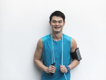 Athlétique Chinois repos après l'exercice. mâle asiatique debout en face d'un mur blanc.
