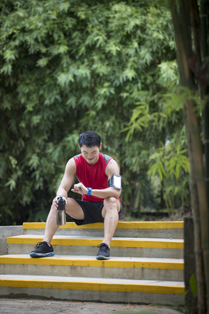 resting heart rate: Asian man out running, using his smart watch heart rate monitor. Fitness healthy lifestyle concept with male athlete.