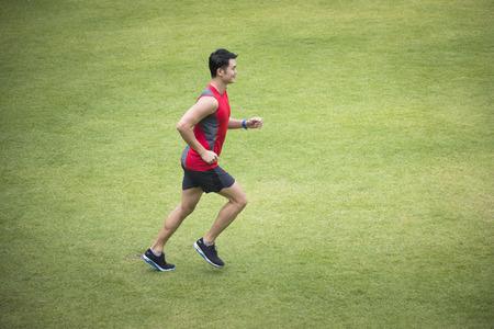 High angle de vue d'un homme chinois sportif du jogging accross un champ d'herbe. concept de remise en forme Homme.