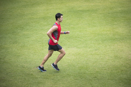 High angle view of a Sporty Chinese man jogging accross a grass field. Male fitness concept. Stock Photo