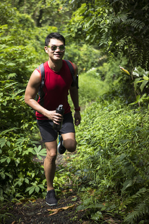 Athletic Asian man trekking on forest trail. Athletic Asian fitness concept.