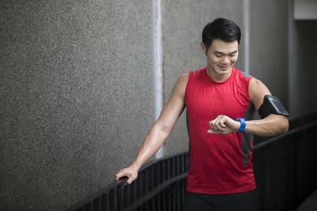 l'homme à la course asiatique, utilisant sa montre intelligente moniteur de fréquence cardiaque. Fitness concept de mode de vie sain avec l'athlète masculin. Banque d'images
