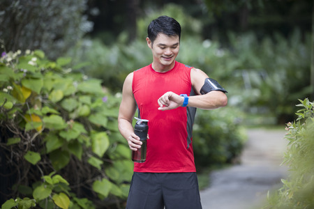 Asian man out running, using his smart watch heart rate monitor. Fitness healthy lifestyle concept with male athlete.