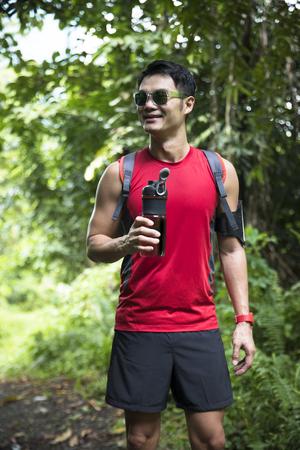 Athletic chinois homme de repos après avoir couru sur le sentier de la forêt. Asiatique mâle coureur prenant pause debout détente.
