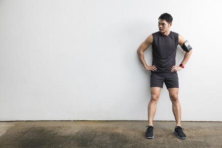 Aziatisch man rust na fitness oefening. Sporty Chinese man staande tegen een witte muur.