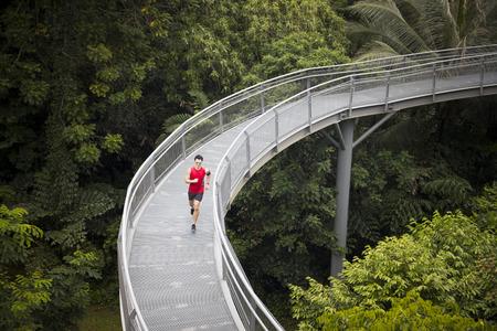High angle de vue d'un homme chinois athlétique jogging sur une forêt canopée. concept de remise en forme Homme.