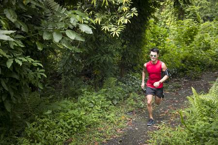 Athlétique, homme asiatique courir sur un sentier forestier. Concept athlétique asiatique de remise en forme. Banque d'images