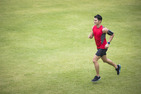 High angle view of a Sporty Chinese man jogging accross a grass field. Male fitness concept. Banque d'images