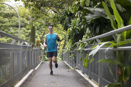 Athletic Asian man running outdoors training for marathon. Athletic Asian fitness concept. Banque d'images