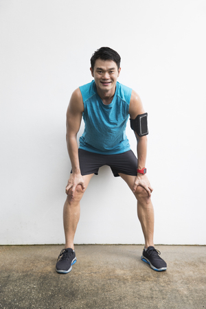Athletic Asian man resting after fitness exercise. Sporty Chinese male standing against a white wall.