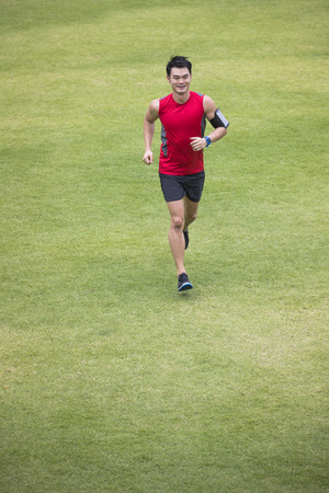 personas corriendo: High angle view of a Sporty Chinese man jogging accross a grass field. Male fitness concept. Foto de archivo