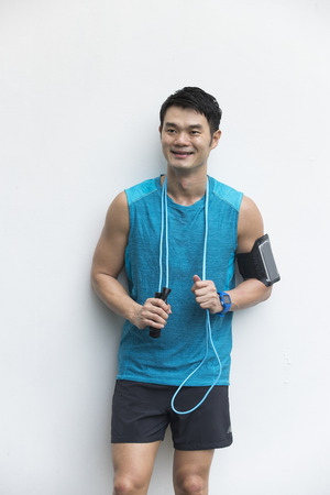 Athletic Chinese man resting after exercise. Asian male standing infront of a white wall. Stock Photo