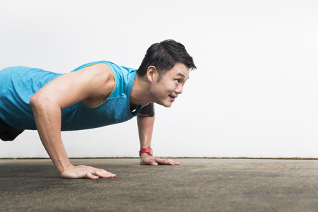 Closeup of an Athletic Asian man stretching during exercising. Action and healthy lifestyle concept.Athletic Asian man doing push up exercise. Action and healthy lifestyle concept.