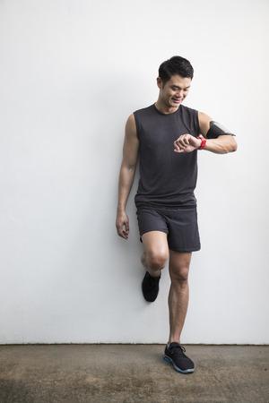 Asiatischer Mann aus Laufen, seine intelligente Uhr Herzfrequenz-Monitor verwenden. Eignung gesunden Lifestyle-Konzept mit männlichen Athleten.
