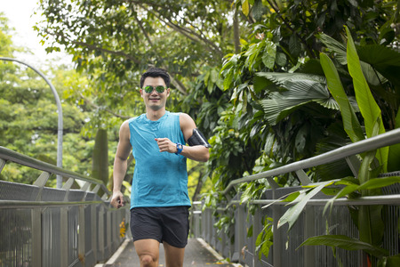 Athletic Asian man running outdoors training for marathon. Athletic Asian fitness concept. Stock Photo