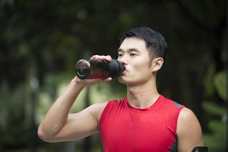 Athletic homme chinois se reposer après course urbaine à travers les rues de la ville. Asiatique mâle coureur prenant pause debout détente.