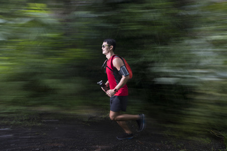 Motion blurred view of an Asian man running on forest trail. Male fitness concept.