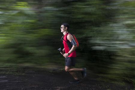 Mouvement floue vue d'un homme asiatique qui court sur le sentier forestier. Concept de fitness masculin. Banque d'images