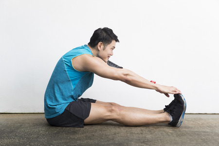 Athletic Asian man stretching during exercising. Action and healthy lifestyle concept. Banque d'images
