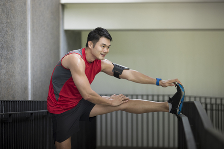 Athletic Asian man stretching during exercising. Action and healthy lifestyle concept. Stock Photo