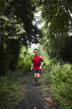 Athletic Asian man running on forest trail. Athletic Asian fitness concept.