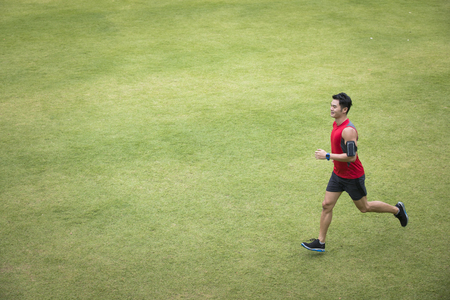 angle: High angle view of a Sporty Chinese man jogging accross a grass field. Male fitness concept. Stock Photo