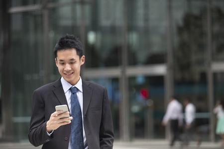 messaging: Asian business man talking reading his smart phone.