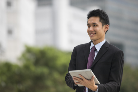 Asian business man using tablet computer outside.