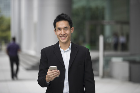 Asian business man talking reading his smart phone.