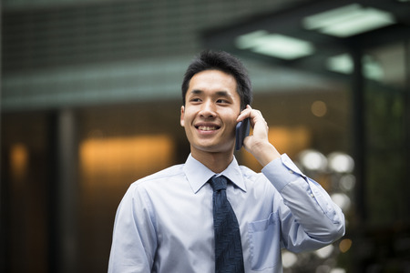 asian business man: Chinese business man talking on a mobile phone.