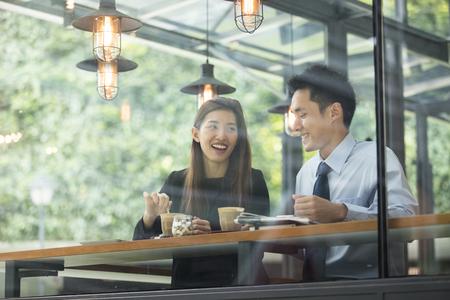 アジア ビジネスの男性と女性のコーヒー ショップで会議します。