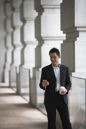 asian business man: Asian business man talking reading his smart phone.