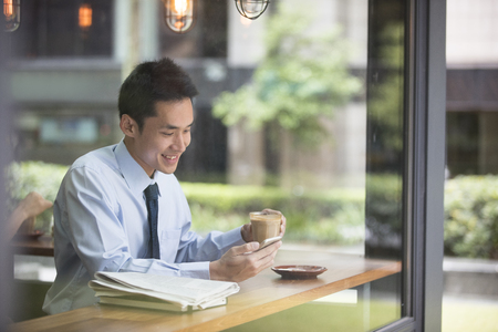 millennial: Asian Businessman with a cup of coffee reading his smart phone in a cafe.