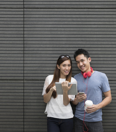 asian girl shopping: Happy Asian man and woman using a digital tablet outdoors.