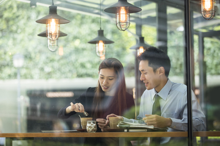 Asian business man and woman meeting in a coffee shop. Banque d'images