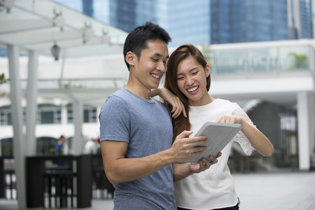 Happy Asian man and woman using a digital tablet outdoors.