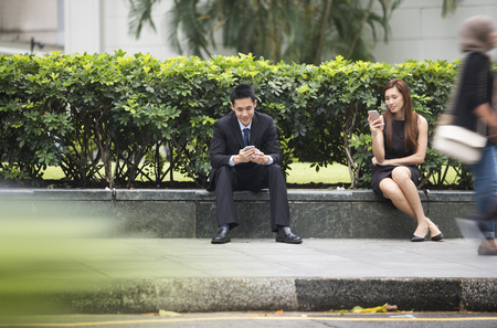 Two Asian business people sitting outdoors looking at there smart phones.