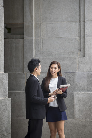 Two Asian Business colleagues talking outside in modern Asian city. Stock Photo