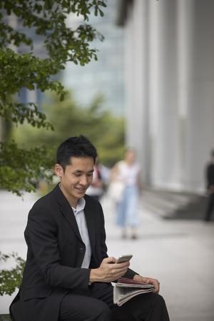 smiling businessman: Asian business man talking reading his smart phone.
